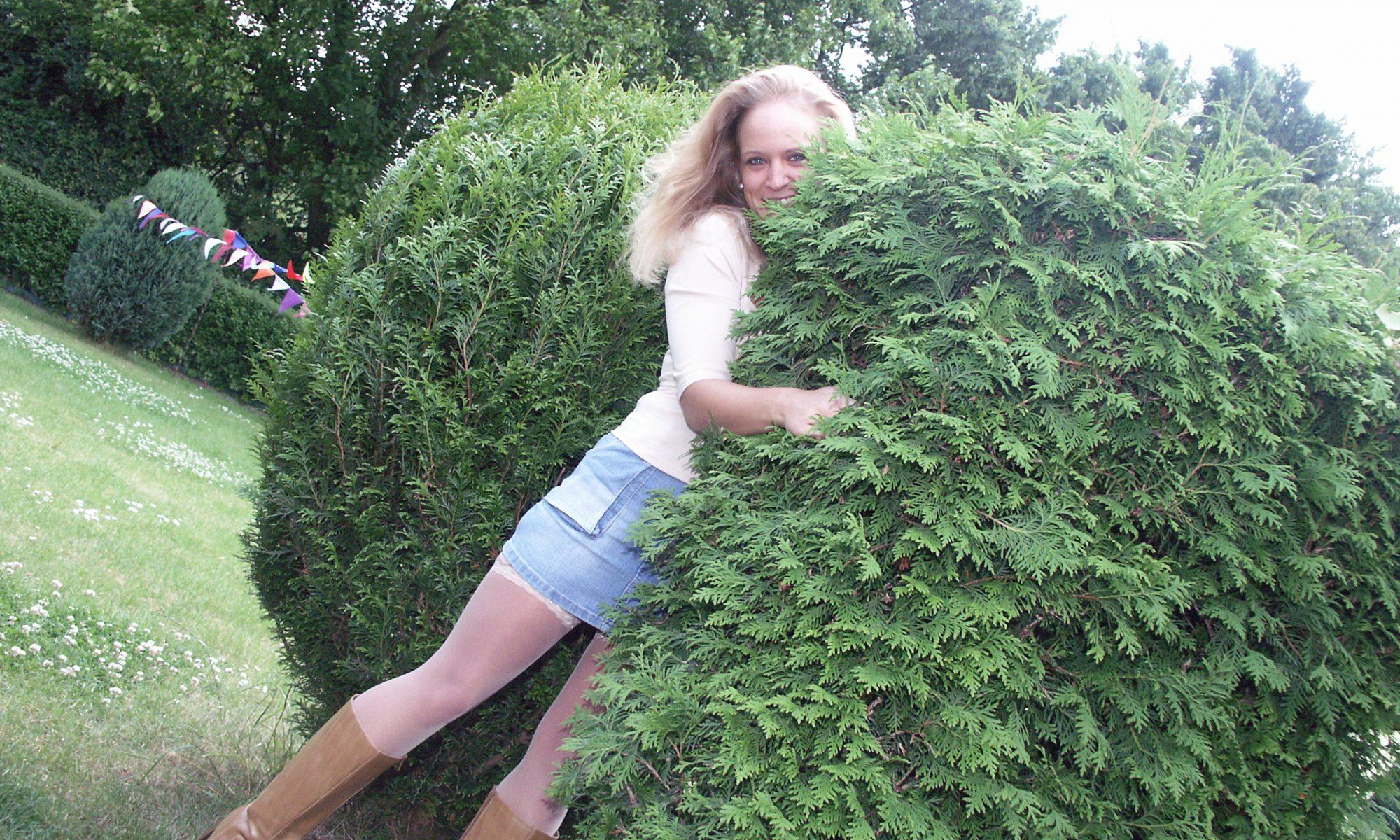Blondine umarmt Gartenhecke